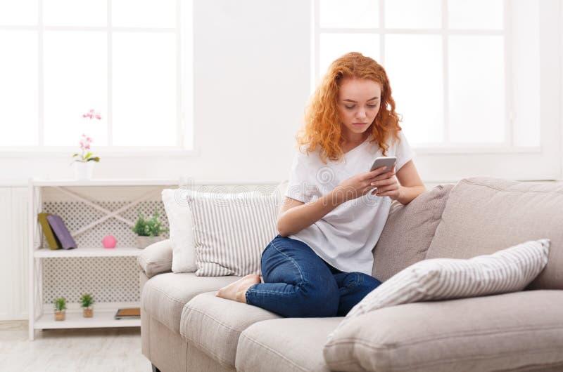 Chica joven pensativa que manda un SMS en smartphone fotos de archivo libres de regalías