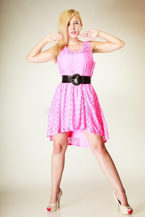 Chica joven preciosa que lleva el vestido rosado corto imagenes de archivo
