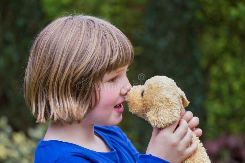 Chica joven que abraza el perro relleno imagenes de archivo