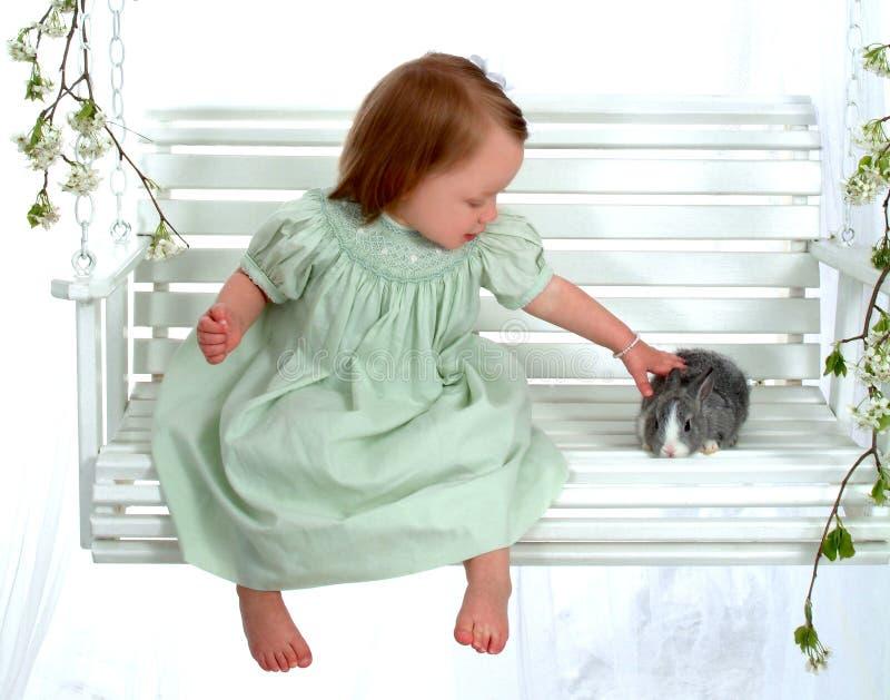 Chica joven que acaricia el conejito fotos de archivo