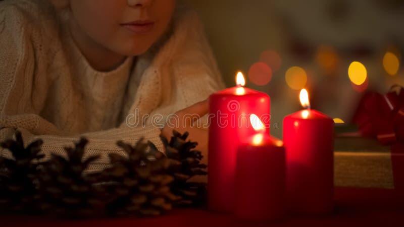 Chica joven que admira las velas de la Navidad, noche antes del día de fiesta, milagro que espera foto de archivo libre de regalías