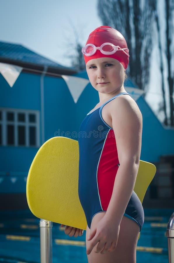 Chica joven que aprende nadar en la piscina con el tablero de la espuma imagen de archivo libre de regalías