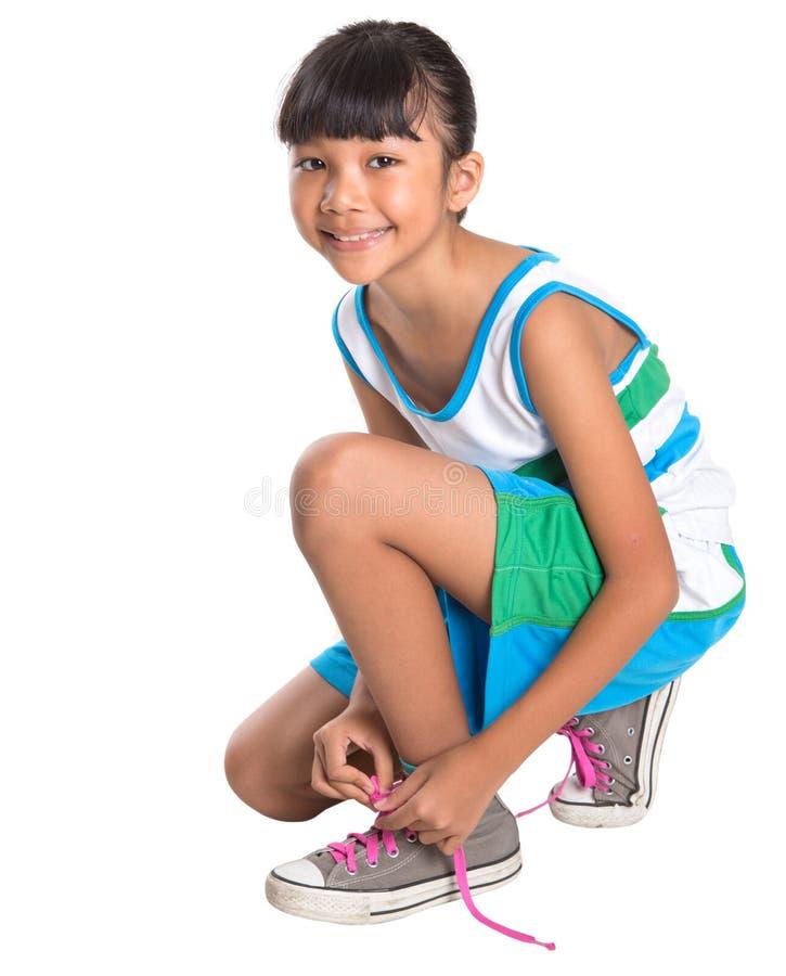 Chica joven que ata cordones de zapato imagenes de archivo
