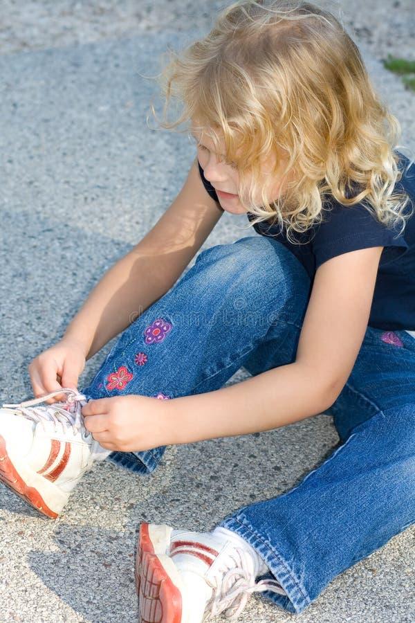 Chica joven que ata su zapato mientras que se sienta. imagen de archivo