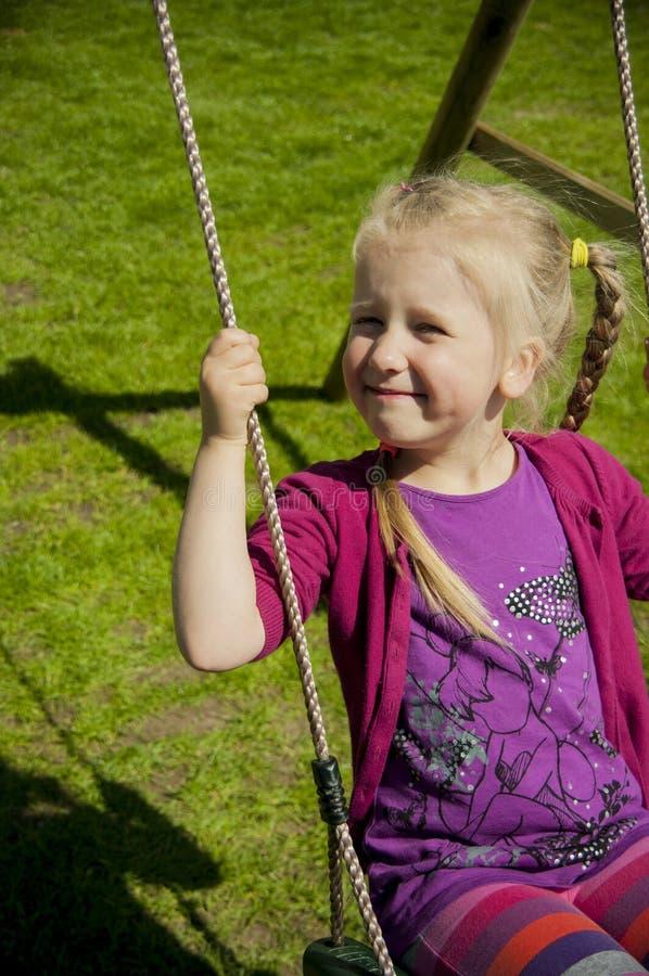 Chica joven que balancea en el patio trasero imagen de archivo