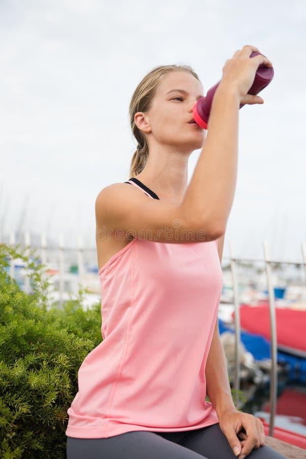 Chica joven que bebe de una botella plástica púrpura fotografía de archivo libre de regalías