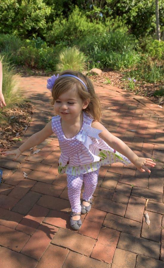 Chica joven que camina y que juega en un jardín botánico imagenes de archivo