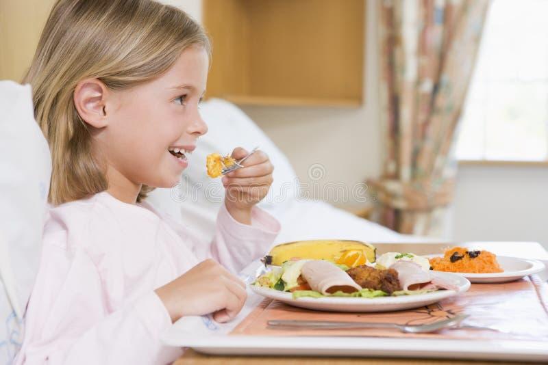 Chica joven que come el alimento del hospital foto de archivo
