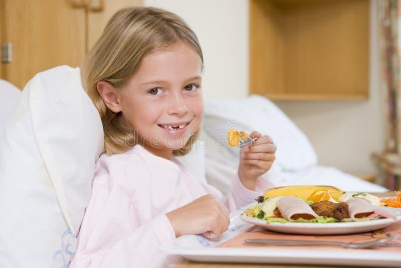 Chica joven que come el alimento del hospital imagenes de archivo
