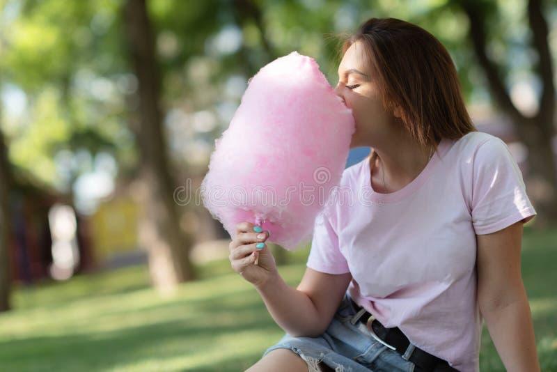 Chica joven que come el caramelo de algodón en el parque imagenes de archivo