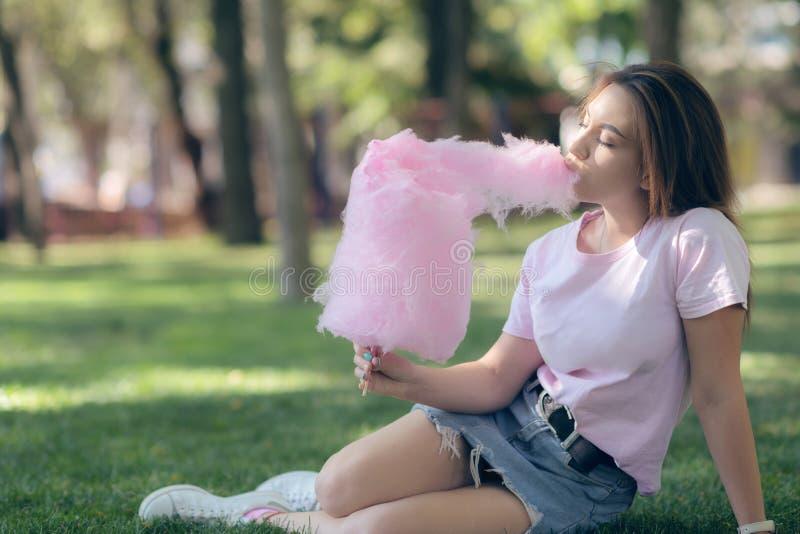 Chica joven que come el caramelo de algodón en el parque fotos de archivo libres de regalías