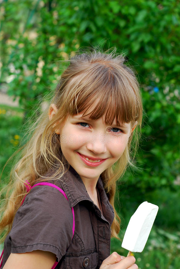 Chica joven que come el helado imagen de archivo