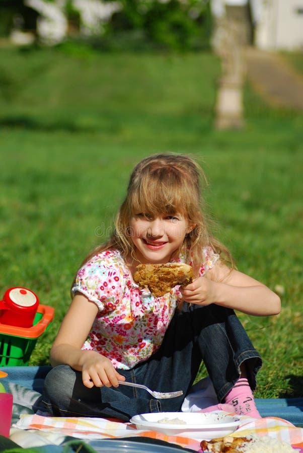 Chica joven que come en comida campestre fotos de archivo libres de regalías