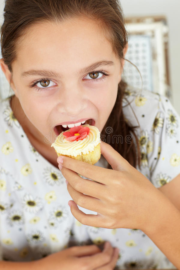 Chica joven que come la magdalena fotografía de archivo