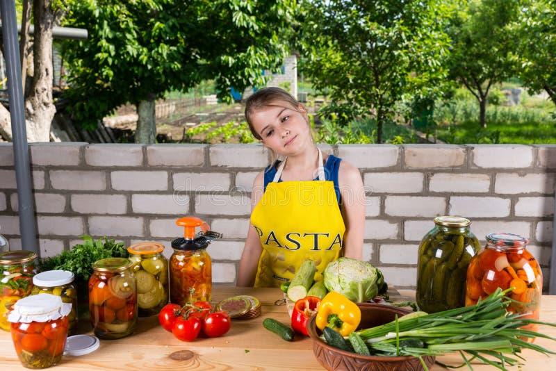Chica joven que conserva verduras frescas en tarros imagen de archivo
