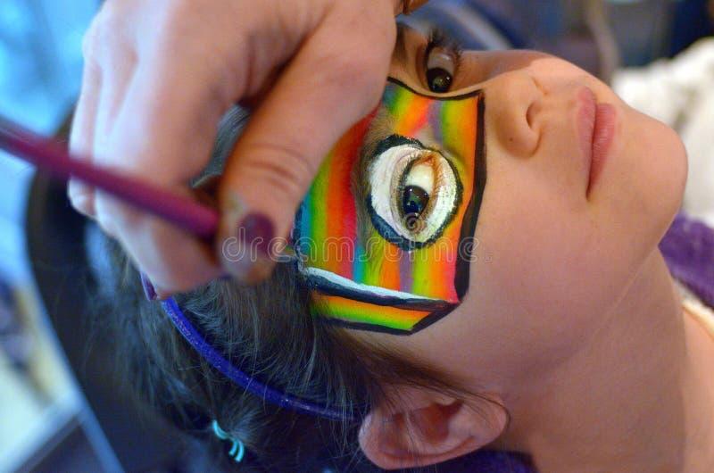 Chica joven que consigue su cara pintada en colores del arco iris imagenes de archivo