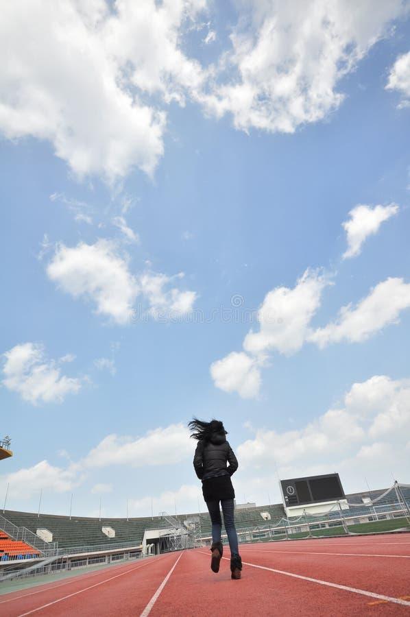 Chica joven que corre en estadio