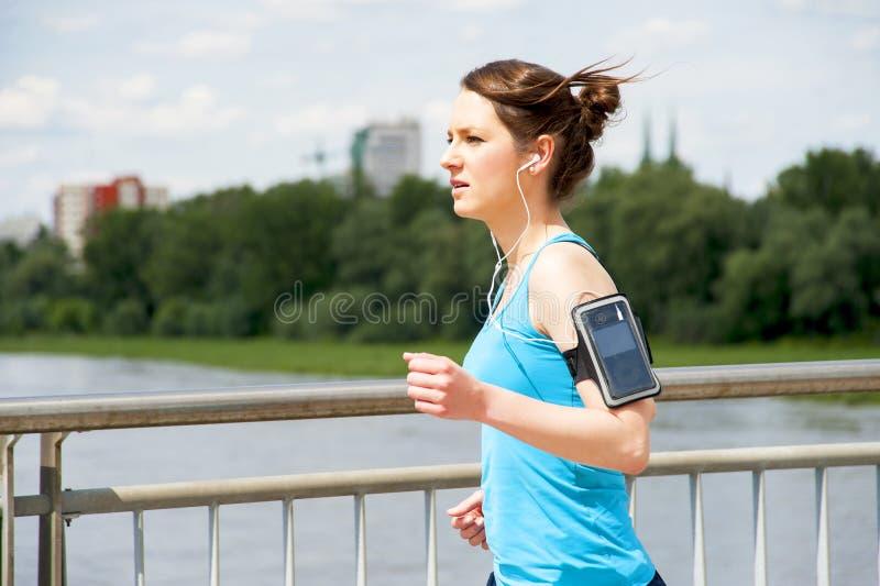 Chica joven que corre en la ciudad, sobre el río por el puente imagen de archivo