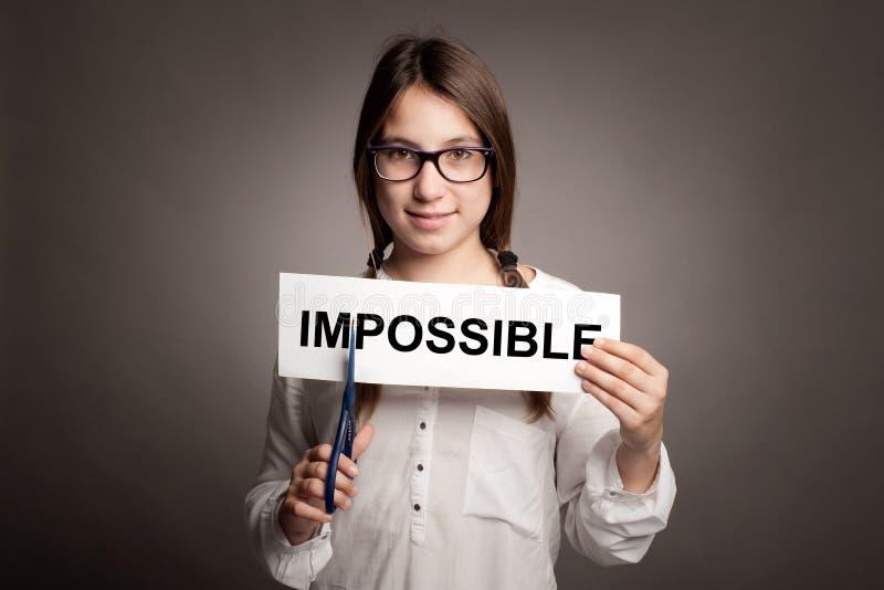 Chica joven que corta palabra imposible fotografía de archivo
