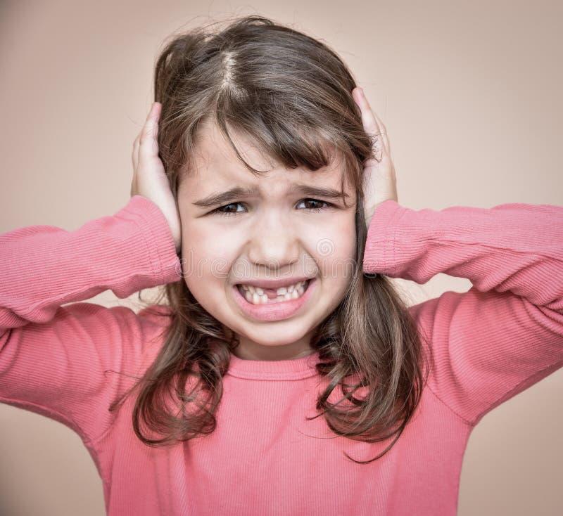 Chica joven que cubre sus oídos foto de archivo libre de regalías