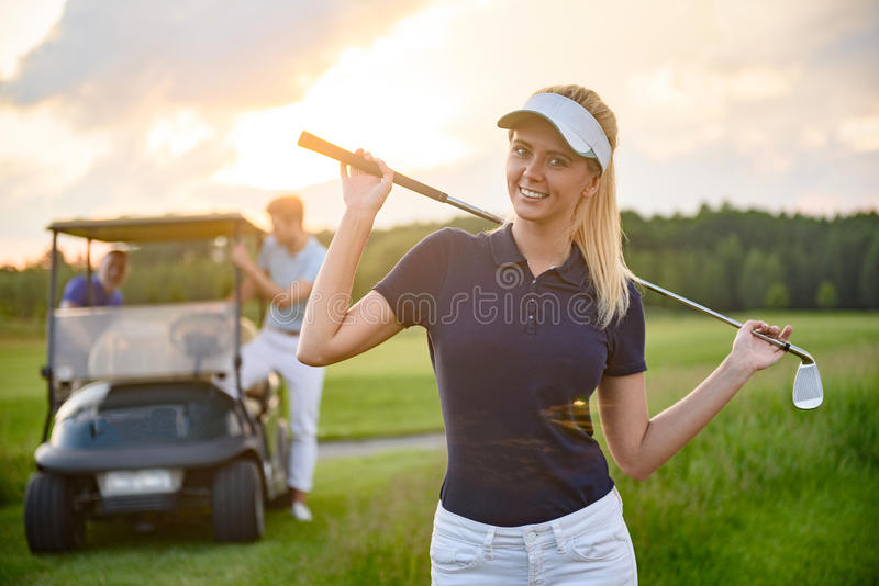 Chica joven que detiene a su club de golf foto de archivo