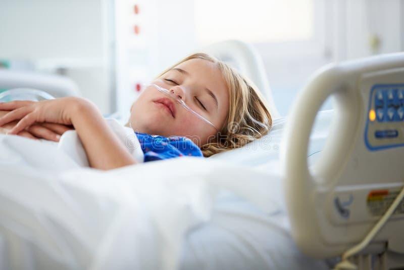 Chica joven que duerme en la Unidad de Cuidados Intensivos foto de archivo