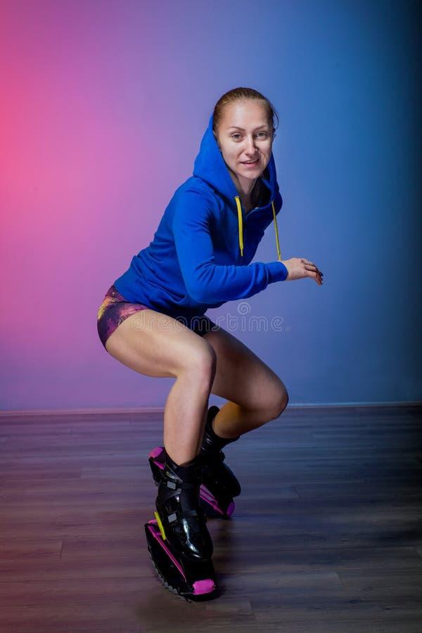 Chica joven que ejercita con los zapatos del kangoo foto de archivo