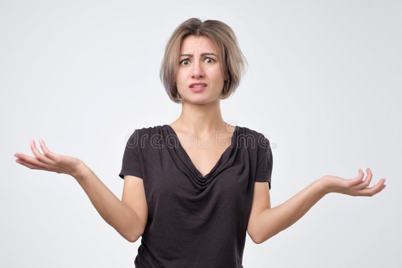 Chica joven que encoge hombros No sé porqué es usted que grita en mí imagen de archivo libre de regalías