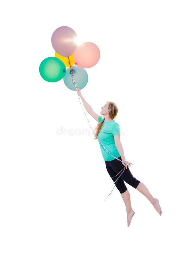 Chica joven que es llevada para arriba y lejos por los globos que ella es HOL imagen de archivo