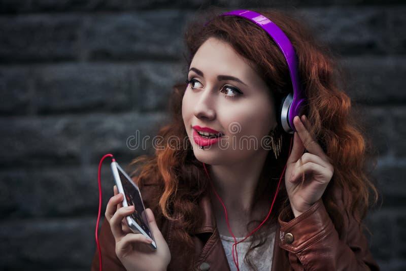 Chica joven que escucha la música con los auriculares en la ciudad, fondo gris imagen de archivo