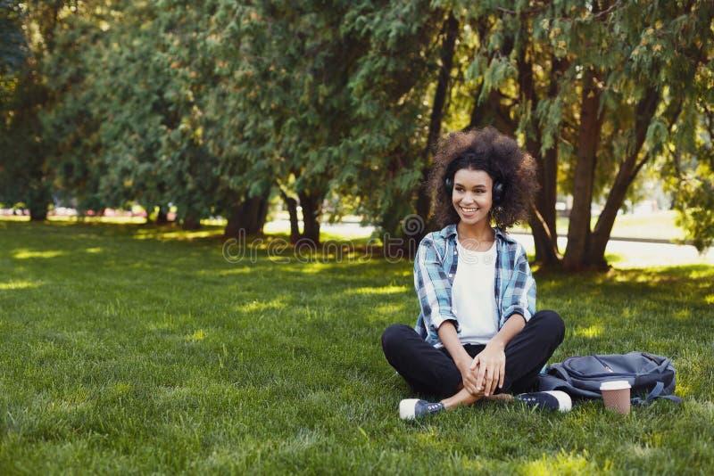 Chica joven que escucha la música en auriculares en el parque fotos de archivo libres de regalías