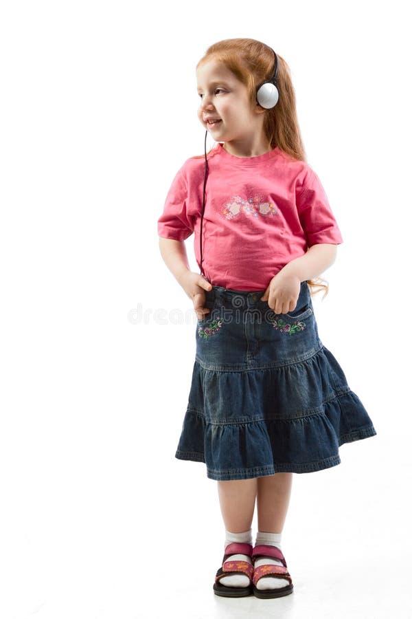 Chica joven que escucha la música en los teléfonos principales imagenes de archivo