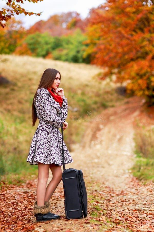 Chica joven que espera en una carretera nacional con su maleta imagenes de archivo