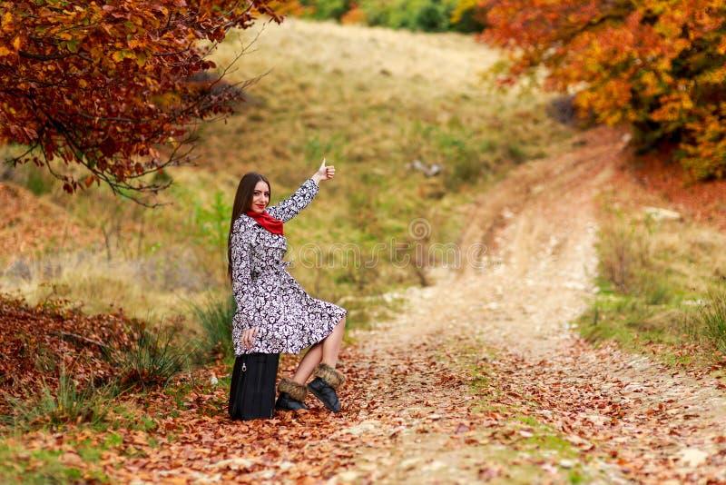 Chica joven que espera en una carretera nacional con su maleta fotos de archivo