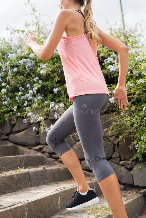 Chica joven que funciona con para arriba pasos de piedra grises fotografía de archivo