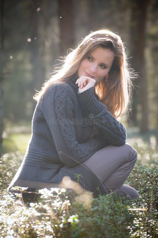 Chica joven que goza del sol de la tarde de la primavera en el bosque fotografía de archivo libre de regalías