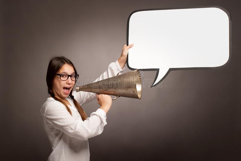 Chica joven que grita con un megáfono viejo imagen de archivo