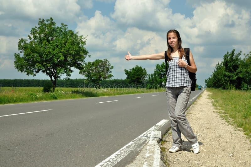 Chica joven que hace autostop en el camino imagen de archivo