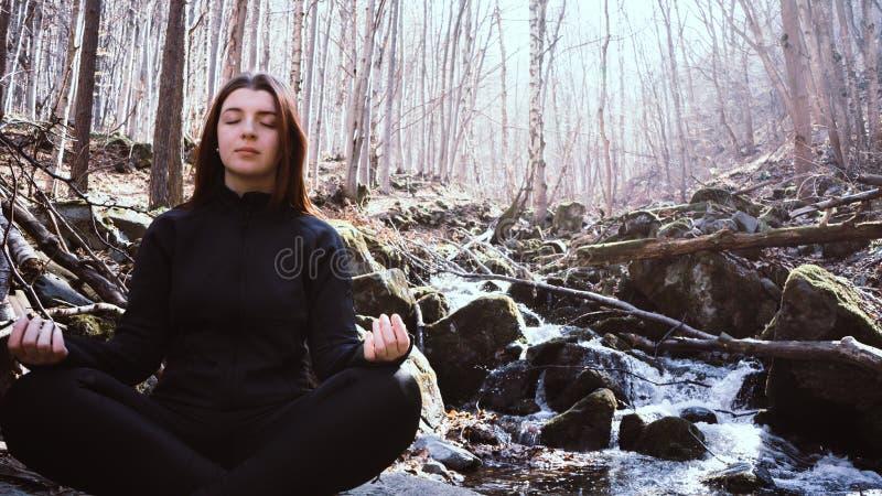 Chica joven que hace el loto de la actitud de la yoga que se sienta en una roca en un r?o que medita en el bosque con luz del sol imagen de archivo libre de regalías