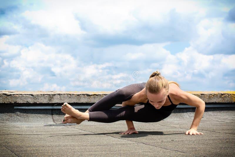 Chica joven que hace la yoga, ashtavakrasana fotografía de archivo libre de regalías