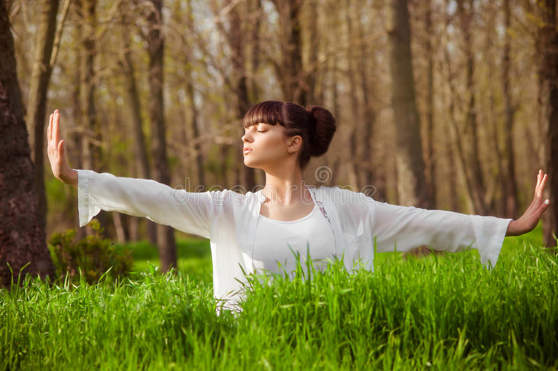 Chica joven que hace yoga en una hierba verde imágenes de archivo libres de regalías
