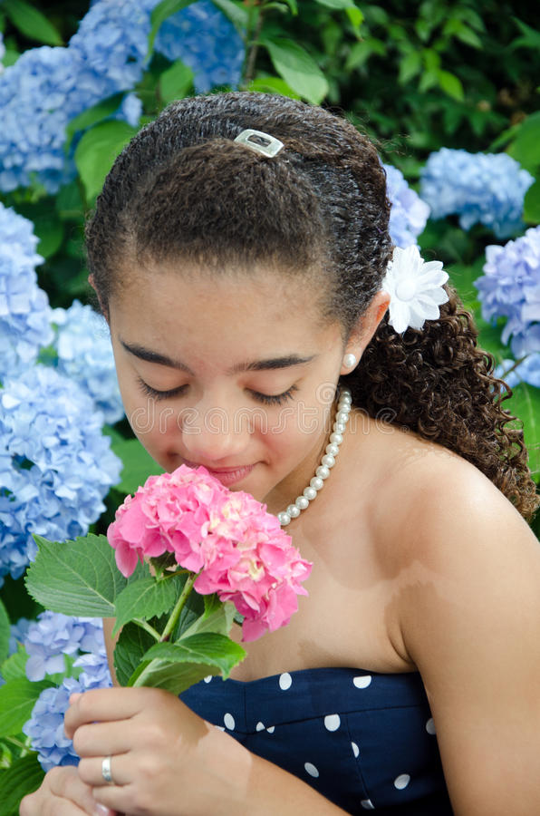 Chica joven que huele la flor rosada foto de archivo
