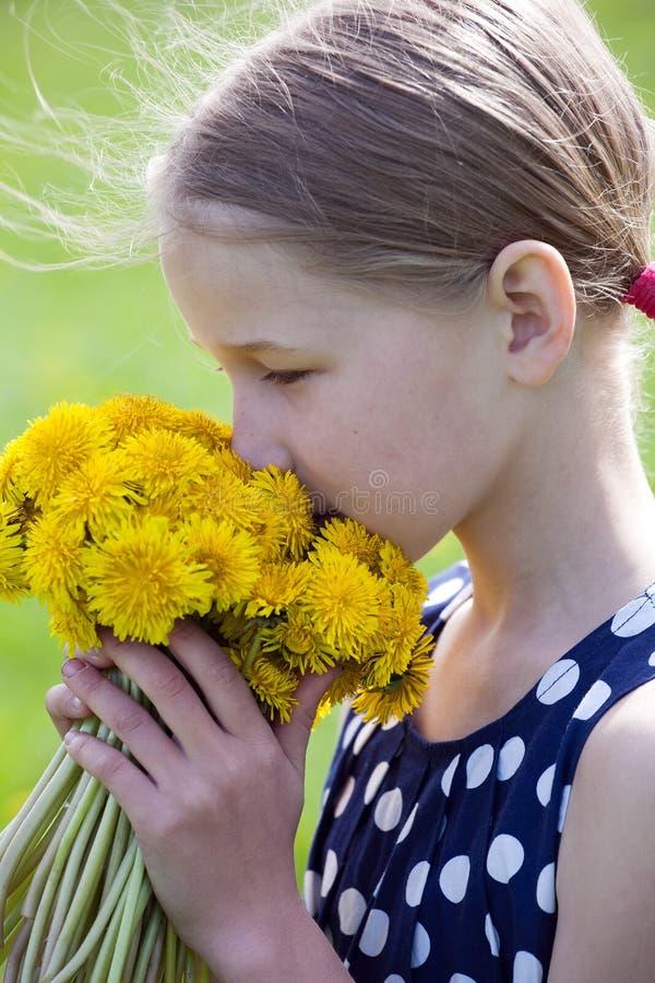 Chica joven que huele un manojo de dientes de león imágenes de archivo libres de regalías