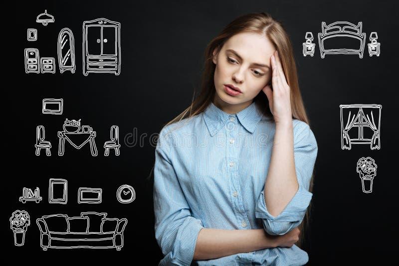 Chica joven que inclina su cabeza mientras que toma una decisión difícil imagen de archivo libre de regalías