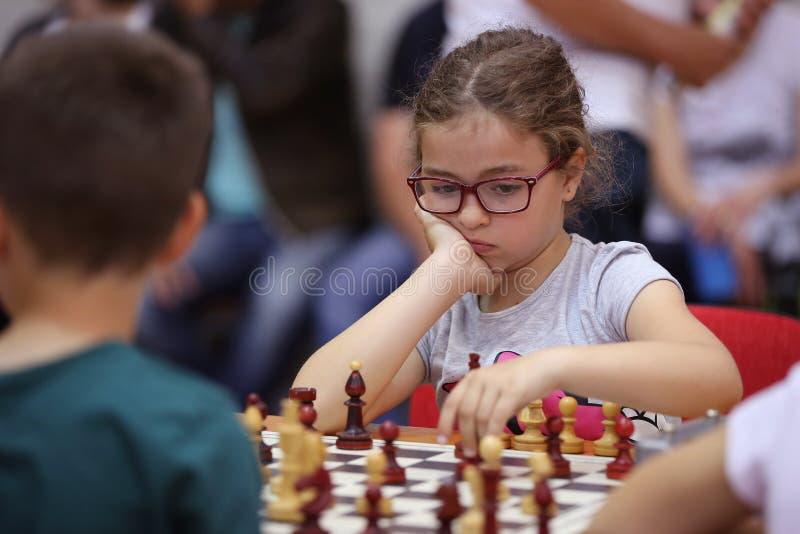 Chica joven que juega a ajedrez fotografía de archivo