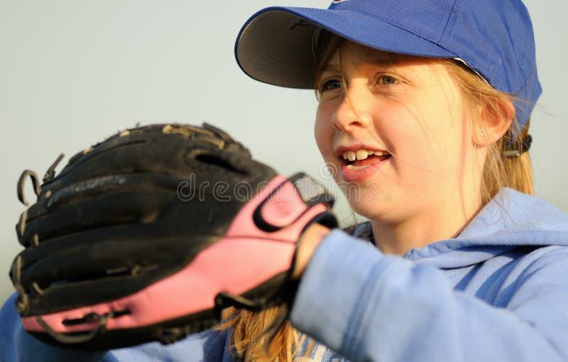 Chica joven que juega a beísbol con pelota blanda foto de archivo