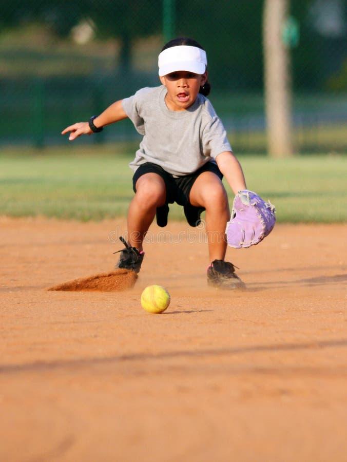 Chica joven que juega a beísbol con pelota blanda fotos de archivo libres de regalías