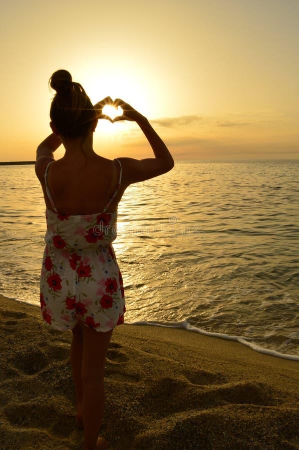 Chica joven que juega con el sol en la playa foto de archivo libre de regalías