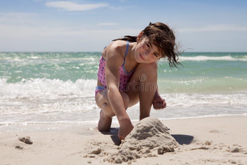 Chica joven que juega en la arena fotos de archivo