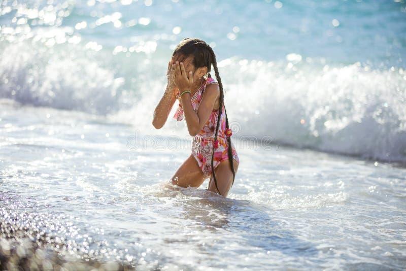 Chica joven que juega en la playa en ondas de fractura y secado de su cara fotografía de archivo